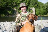 Traveler with a Rhodesian Ridgeback by the river.