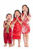 Group of oriental children wishing you a happy Chinese New Year, with traditional Cheongsam full len