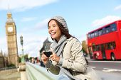 stock photo of palace  - London tourist woman sightseeing taking pictures near Big Ben with red double decker bus - JPG