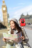 London tourist woman sightseeing holding map near Big Ben with red double decker bus. Tourism travel