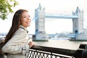 London woman happy on Tower Bridge. Multicultural young professional smiling and laughing enjoying view of River Thames. Beautiful female tourist on travel in England, Great Britain.