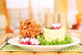 Chicken Kiev on croutons with mashed potatoes, on wooden table, on bright background