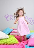 Little girl jumping on bed in room on grey wall background