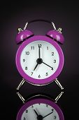 Purple alarm clock on dark purple background