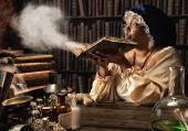Medieval alchemist blowing dust off the old books in her laboratory