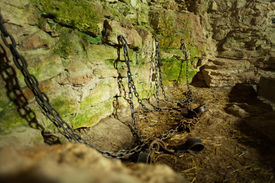 stock photo of dungeon  - Castle dungeon prison with chains chain and moss on stone walls - JPG