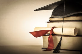picture of scroll  - A mortarboard and graduation scroll tied with red ribbon on a stack of old battered book with empty space to the left - JPG