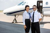 Portrait of happy airhostess and pilot standing against private jet at terminal