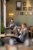 Side view of pregnant woman having coffee while looking away at cafe
