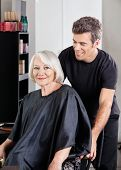 Portrait of senior female client with hairstylist standing behind at salon