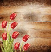 Bouquet Of Red Tulips With Green Leaves On Abstract Wooden Background