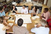 image of pacific islander ethnicity  - Group Of Architects Sitting Around Table Having Meeting - JPG