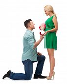 happiness, proposal, engagement and celebration concept - smiling couple with flower bouquet and rin