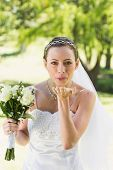 Portrait of young bride with bouquet blowing kiss in garden