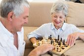 Senior couple sitting on floor playing chess at home in living room