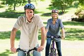 Happy couple riding bicycles in park