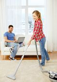 home, relations and cleaning concept - smiling woman with hoover and young man with laptop at home