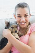 Smiling woman cuddling her yorkshire terrier on the couch at home in the living room