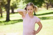 Portrait of a displeased young girl gesturing thumbs down at the park