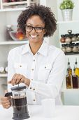 A beautiful happy mixed race African American girl or young woman making coffee with a cafetiere in