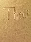 The word Thai is written on a sand background