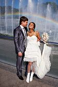 Happy Bride And Groom Near Fountain With Rainbow