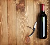 Red wine bottle and corkscrew on wooden table background with copy space