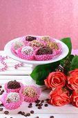 Set of chocolate candies on table on pink background