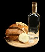 Bottle of vodka, fresh bread and glass on wooden board, isolated on black