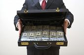 Mid section view of businessman holding briefcase with full of money