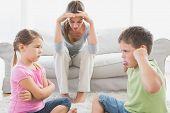 Fed up mother listening to her young children fight at home in the living room