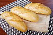 Three Long Loafs  On A Chopping Board