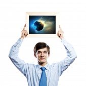 Handsome businessman holding frame with Earth planet. Elements of this image are furnished by NASA
