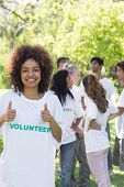 Confident female volunteer gesturing thumbs up with friends disucssing in background