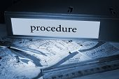 The word procedure on blue business binder on a desk