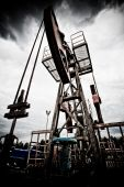 stock photo of nonrenewable  - Oil rig pump dramaticly underexposed against contrast cloudy sky low angle view - JPG