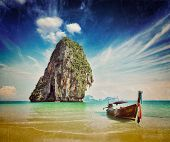 Retro vintage hipster style image of tropical vacation holiday beach concept - Long tail boat on tropical beach, Krabi, Thailand with grunge texture overlaid