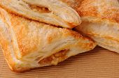 Closeup of Apple Turnovers ona brown paper surface. Horizontal format filling the frame.