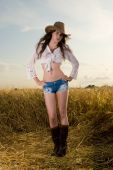 Slavonic girl in cowboy clothes pose in wheat field
