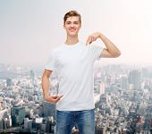 gesture, advertising and people concept - smiling young man in blank white t-shirt pointing fingers on himself over city background