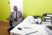Indian businessman asleep at his desk clutching ukulele