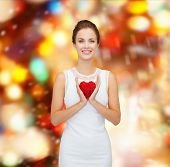 happiness, health, charity and love concept - smiling woman in white dress with red heart over party lights background