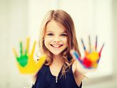 education, school, art and painitng concept - smiling little student girl showing painted hands at s