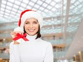 christmas, holidays, winter, consumerism and people concept - smiling woman in santa helper hat with