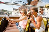 friendship, travel, vacation, summer and people concept - group of smiling friends with map travelin