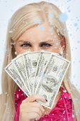 Blonde hiding her face with dollars banknotes against snow falling