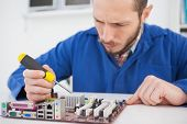 Computer engineer working on cpu with screwdriver in his office