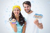 Happy young couple painting together against snow falling