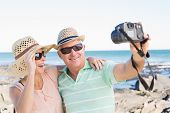 foto of take off clothes  - Happy casual couple taking a selfie by the coast on a sunny day - JPG