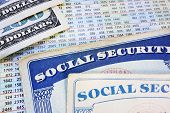 stock photo of social-security  - Social Security cards with cash and benefit amount numbers - JPG